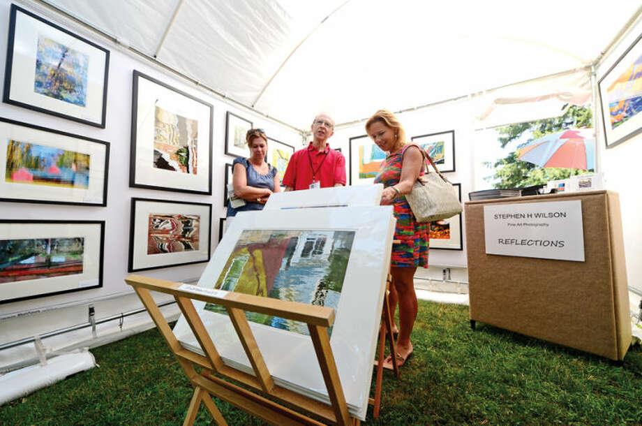 Hour photo / Erik Trautmann Photographer Stephen Wilson and visitors Lisa Vacheron and Barbara Cronin talk photography during the 2nd annual Norwalk Art Festival at Mathews Park Saturday.