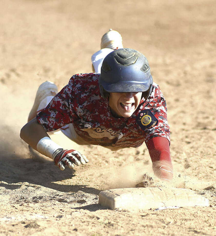 Hour photo/John NashNorwalk Post 12 Junior Legion player Matt Galyas dives back into first base on a pick-off attempt in Thursday's state tournament game in Branford.