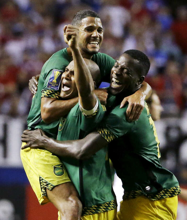 Jamaica's Joel McAnuff, top, Rudolph Austin, lower left, and Je-Vaughn Watson, right, celebrate after Jamaica defeated the United States 2-1 in a CONCACAF Gold Cup soccer semifinal Wednesday, July 22, 2015, in Atlanta. (AP Photo/David Goldman)