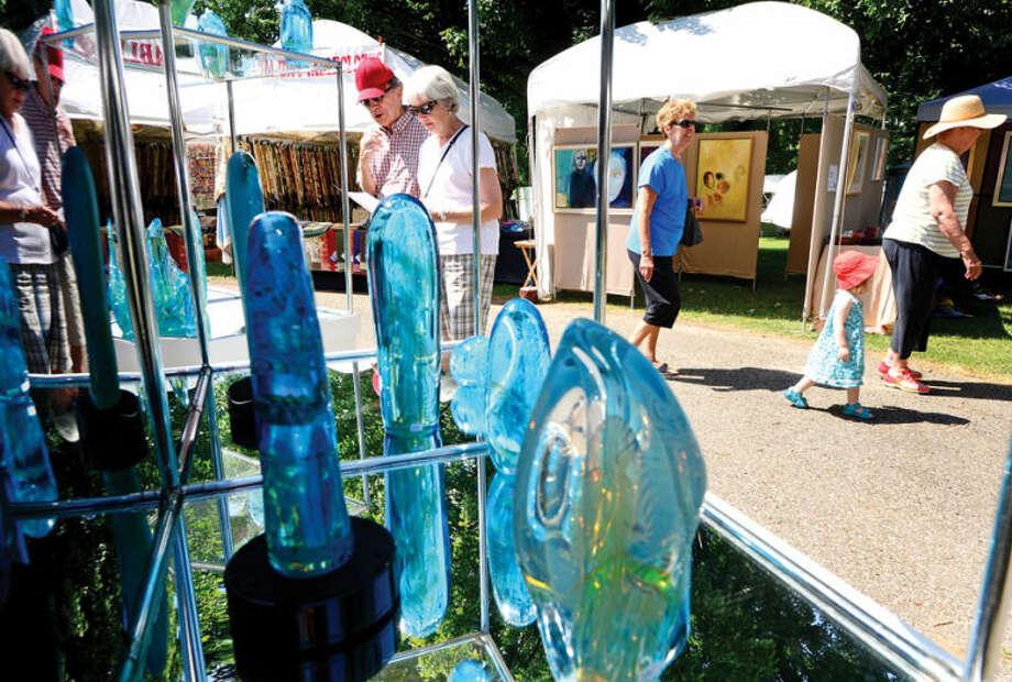 Hour photo / Erik Trautmann Visitors browse artist kiosks during the 2nd annual Norwalk Art Festival at Mathews Park Saturday.