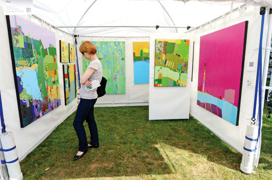 Hour photo / Erik Trautmann Nadine Greenwood checks out the mixed media paintings from Tom Hlas during the 2nd annual Norwalk Art Festival at Mathews Park Saturday.