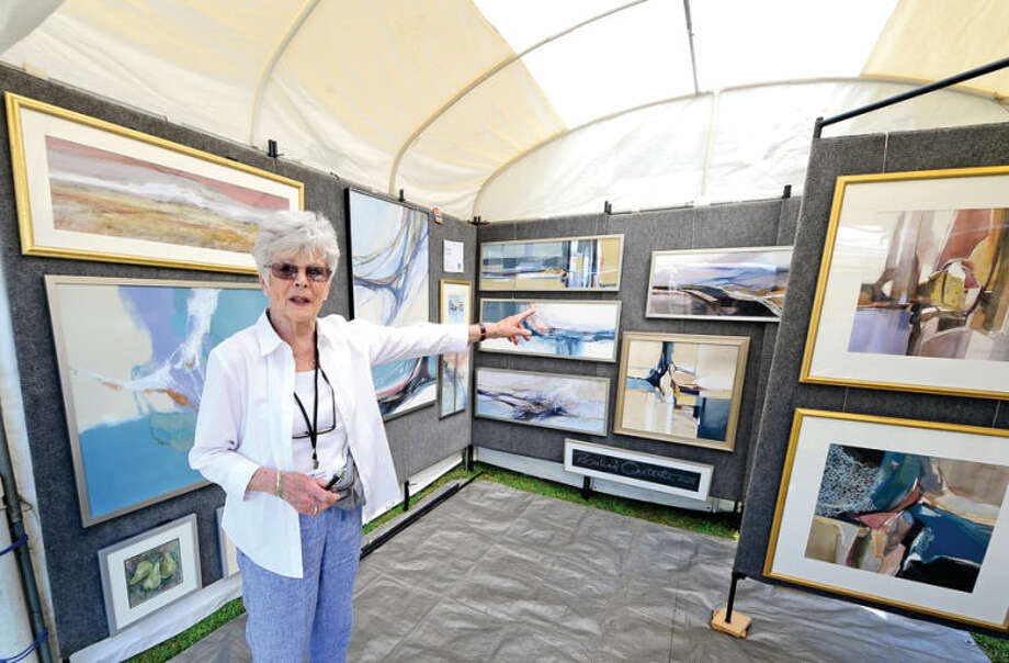 Hour photo / Erik Trautmann Artist Rosalind Oesterle poits out her favorite works during the 2nd annual Norwalk Art Festival at Mathews Park Saturday.
