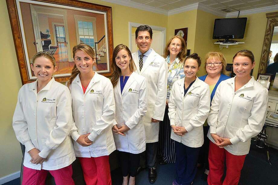 Dr. James Aris with his wife, Pamela, center, and staff. From left to right are: Laura Clements, Carly Herrera, Dr. Jaqueline Bonanno, Natalie Wall, Judy Klem and Tanya Ralph in their Wilton office.