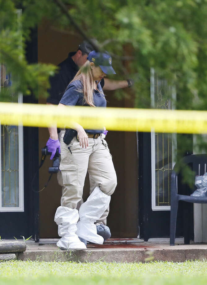An investigator walks around blood on the doorstep of a house in Broken Arrow, Okla., Thursday, July 23, 2015, where five family members were discovered stabbed to death. Two teenagers were taken into custody. (AP Photo/Sue Ogrocki)