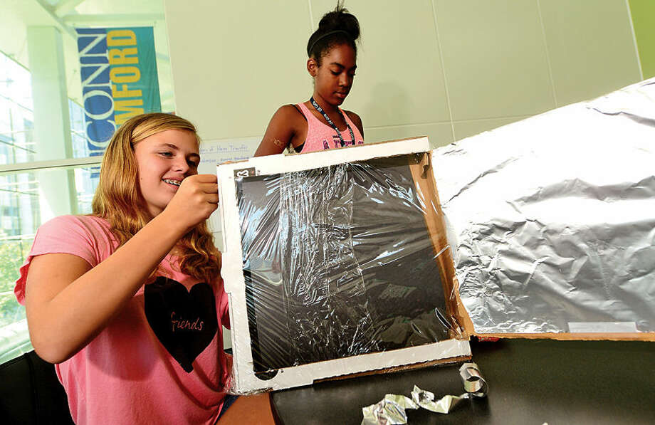 Thirty middle school girls from Stamford Public Schools including Bridget Sypniewski and Srenity Woddy, both 12, build a solar oven out of pizza boxes Tuesday as they spend the week in GE Girls at UCONN, a five-day learning program where they explore hands-on science, technology, engineering and math (STEM).