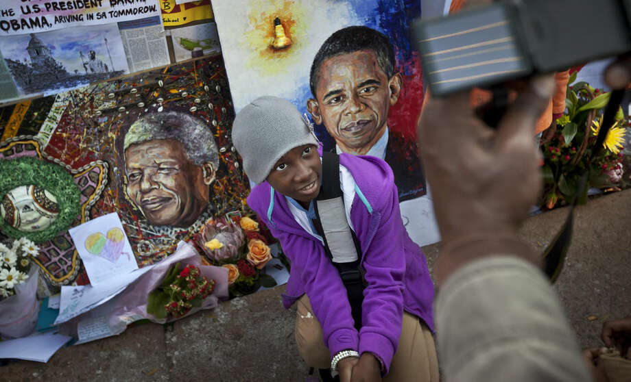 FILE - In this Saturday June 29, 2013 file photo, children squat to have their photograph taken by their parents next to paintings of President Barack Obama, center, and former South African President Nelson Mandela, left, outside the Mediclinic Heart Hospital where Nelson Mandela is being treated in Pretoria, South Africa. Barack Obama, the United States' first African-American president, has captured the imagination of people across the continent where his face shows up on billboards, backpacks, T-shirts and restaurants. On Friday, July 24, 2015 Obama will be visiting Kenya, where his father was born, for a summit on entrepreneurship before heading to Ethiopia to address leaders at the African Union headquarters. Wherever he goes, large crowds are expected to gather and cheer him. (AP Photo/Ben Curtis, file)