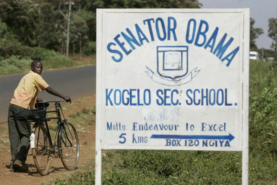 FILE - In this Tuesday, Feb. 5, 2008 file photo, a boy pushes his bicycle past a sign for the Senator Obama secondary school in the village of Kogelo, Kenya where Barack Obama's grandmother lives. Barack Obama, the United States' first African-American president, has captured the imagination of people across the continent where his face shows up on billboards, backpacks, T-shirts and restaurants. On Friday, July 24, 2015 Obama will be visiting Kenya, where his father was born, for a summit on entrepreneurship before heading to Ethiopia to address leaders at the African Union headquarters. Wherever he goes, large crowds are expected to gather and cheer him.(AP Photo/Ben Curtis, file)