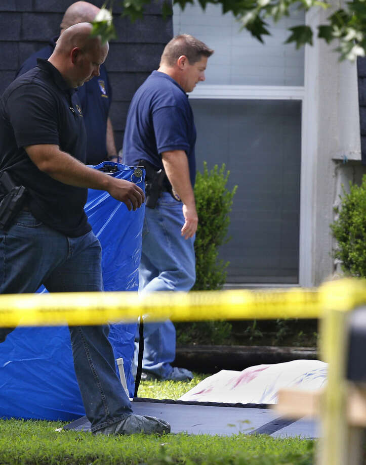 Investigators work in the front yard of a home in Broken Arrow, Okla., Thursday, July 23, 2015, where five people were discovered stabbed to death. Two teenagers were taken into custody. (AP Photo/Sue Ogrocki)