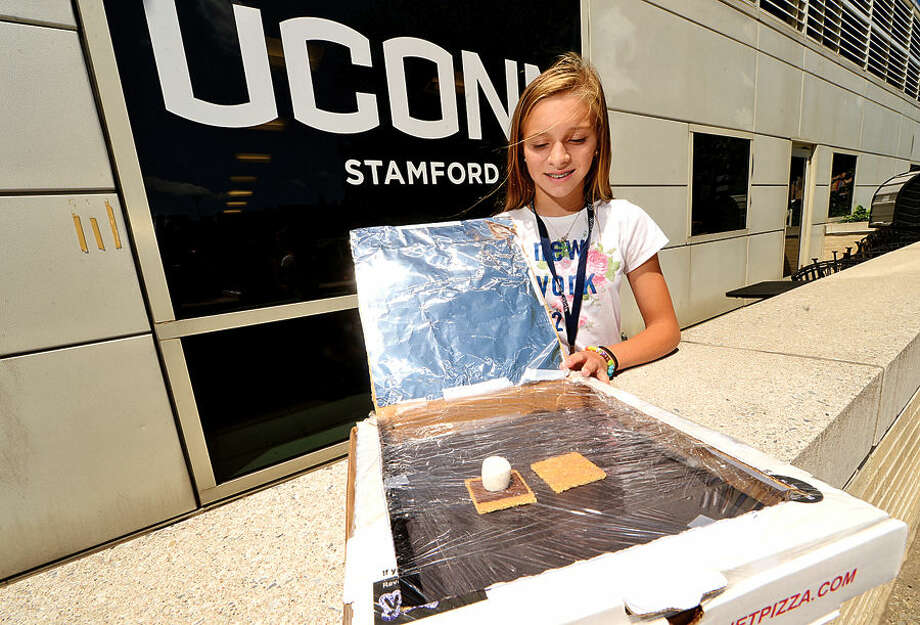 Kaily Young, 13, looks to melt a smore after building a solar oven out of a pizza box Tuesday as 30 middle school girls from Stamford Public Schools spend the week in GE Girls at UCONN, a five-day learning program where they explore hands-on science, technology, engineering and math (STEM).