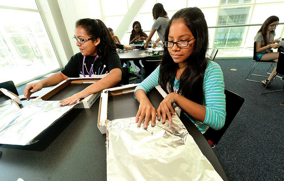 Thirty middle school girls from Stamford Public Schools including Susan Arana and Jocelyn Coloantes, both 13, build a solar oven out of pizza boxes Tuesday as they spend the week in GE Girls at UCONN, a five-day learning program where they explore hands-on science, technology, engineering and math (STEM).
