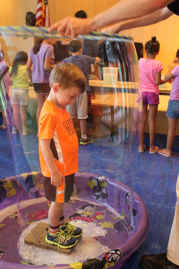 """Three-year old Bryce Joy finds himself totally encased in a giant bubble during Wilton Library's Wonderful Wednesdays Bubble Technology program, part of the library's """"Everything STEMs from Reading"""" summer reading program for kids."""