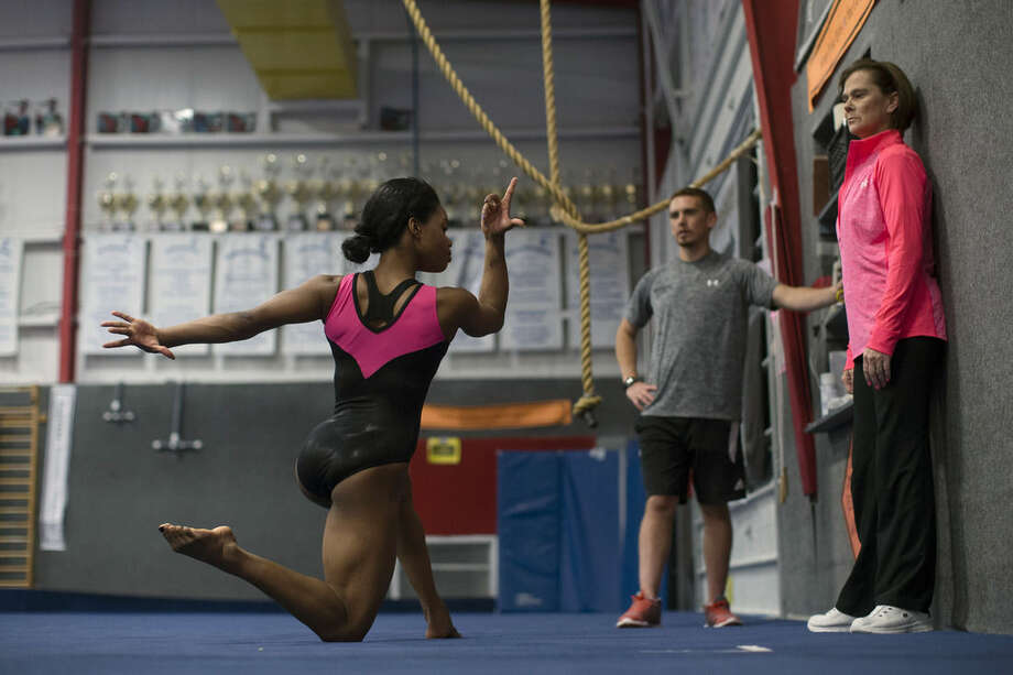 ADVANCE FOR WEEKEND EDITIONS, JULY 24-26 - In this July 17, 2015, photo, defending women's Olympic all-around gymnastics champion Gabby Douglas practices her floor routine as coach Kittia Carpenter, right, looks on at Buckeye Gymnastics in Westerville, Ohio. Thirteen months before the flame is lit in Rio de Janiero, Douglas will compete in the U.S. for the first time since the 2012 Olympic Trials on Saturday, July 25, when she takes the floor for the Secret Classic in Chicago. (AP Photo/John Minchillo)