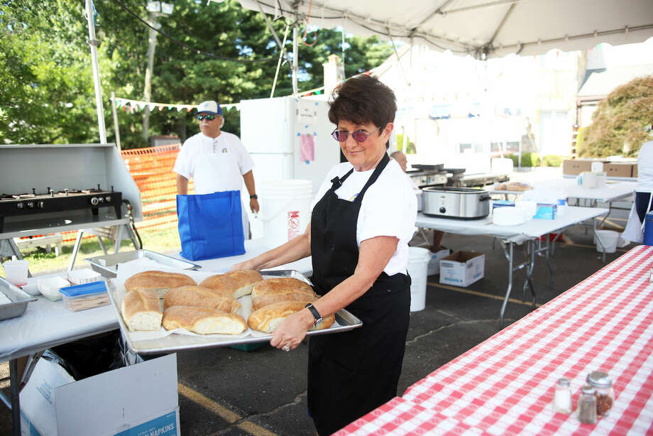 Barbara Toscano brings out the home made bread to go with ziti during the annual St. Ann Festival in Norwalk Friday afternoon. Hour Photo / Danielle Calloway