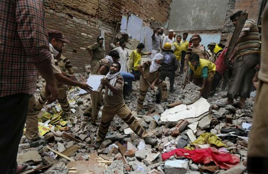 Rescue workers clear debris at the site of a building collapse in New Delhi, India, Saturday, June 28, 2014. A dilapidated building collapsed in the Indian capital on Saturday, killing at least seven people as rescuers searched for others believed to be trapped. (AP Photo/Altaf Qadri)