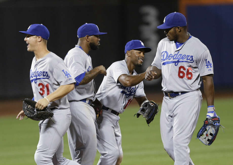 Los Angeles Dodgers' Yasiel Puig (66) celebrates with Jimmy Rollins (11), Howie Kendrick and Joc Pederson (31) after a baseball game against the New York Mets on Friday, July 24, 2015, in New York. The Dodgers won 7-2. (AP Photo/Frank Franklin II)