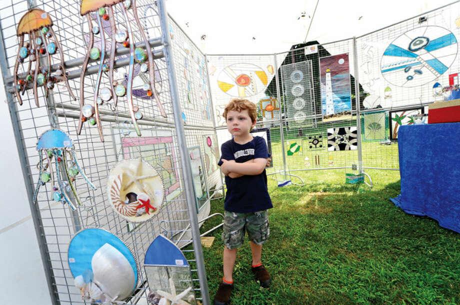 Hour photo / Erik Trautmann Colt Hotchkiss, 3, examines glass scuptures by Jennifer Webb during the 2nd annual Norwalk Art Festival at Mathews Park Saturday.