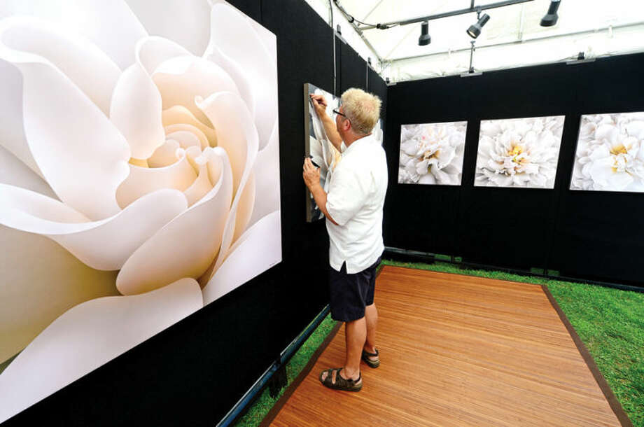 Hour photo / Erik Trautmann Artist Edward Loedding touches up some of his work during the 2nd annual Norwalk Art Festival at Mathews Park Saturday.