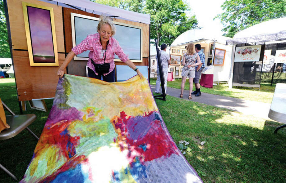 Hour photo / Erik Trautmann Hanneke der Neve unfurls a tapestry she made for the 2nd annual Norwalk Art Festival at Mathews Park Saturday.