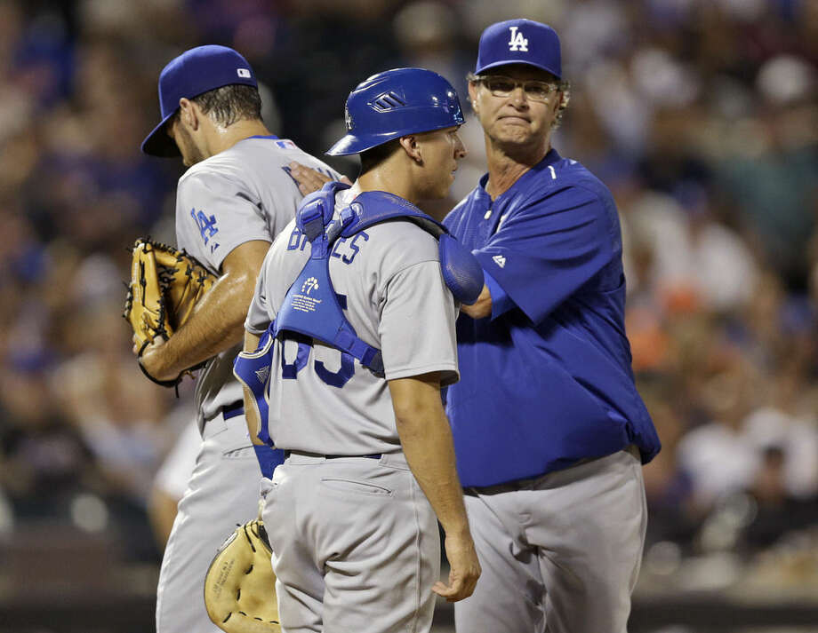Los Angeles Dodgers manager Don Mattingly, right, takes relief pitcher Josh Ravin, left, out of the game as catcher Austin Barnes (65) looks away during the seventh inning of a baseball game Saturday, July 25, 2015, in New York. (AP Photo/Frank Franklin II)