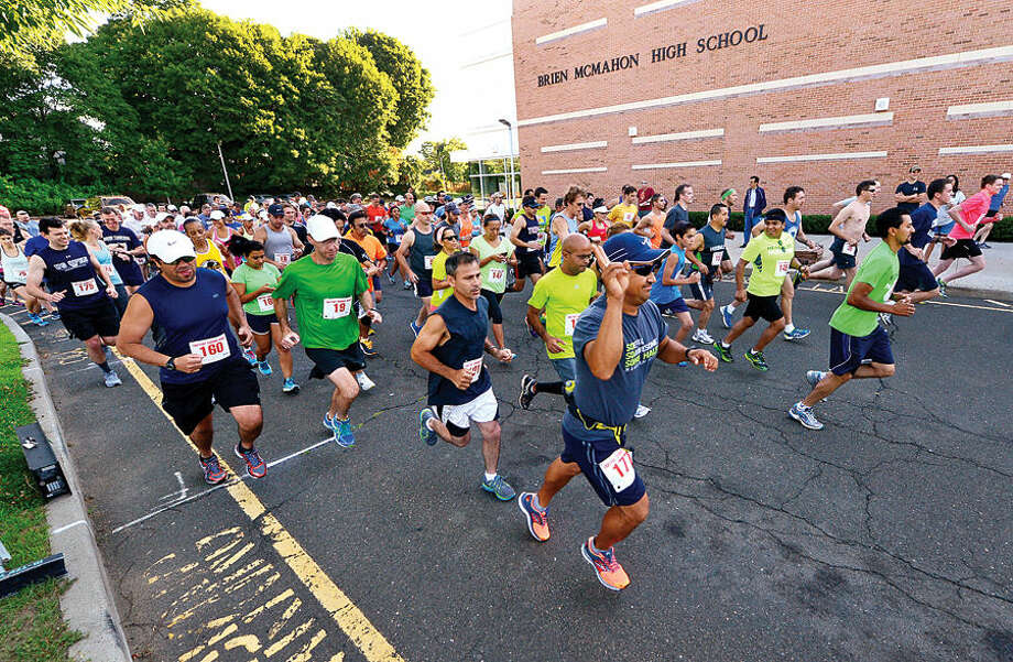 Hour photo / Erik Trautmann iNorwalk Lightfoot runners start out on the club's 7-mile road race at Brien McMahon High School Saturday.