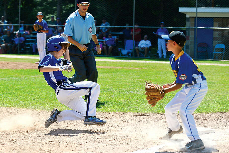 Hour photo / Erik Trautmann Norwalk player Brendan Edvardsen roles into third with a triple during the Cal Ripken 11s state championship game vs Newtown Saturday at Tim Devine Field in Norwalk