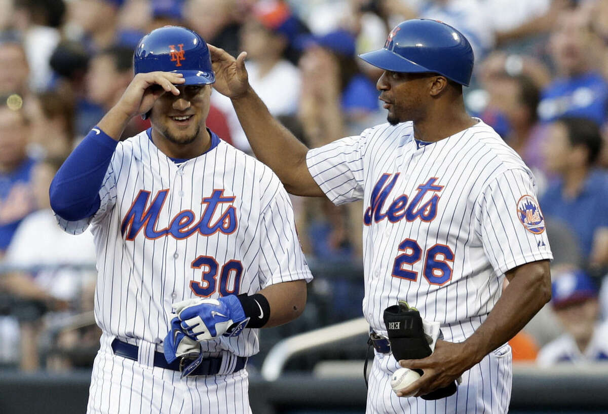 New York Mets first base coach Tom Goodwin (26) congratulates Michael Conforto (30) on his first major league base hit during the first inning of a baseball game against the Los Angeles Dodgers, Saturday, July 25, 2015, in New York. (AP Photo/Frank Franklin II)