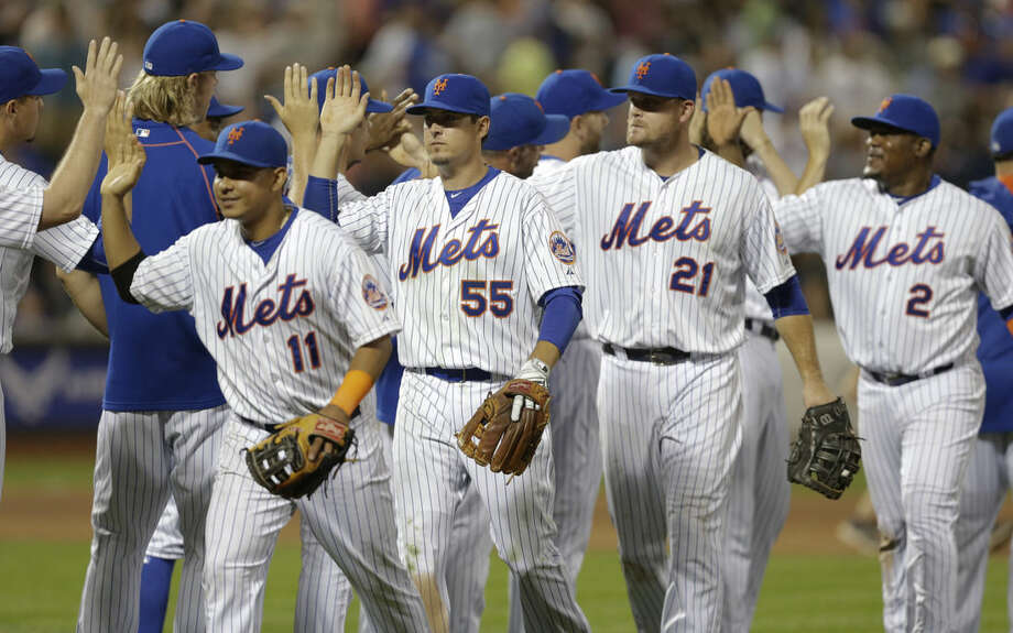 New York Mets' Ruben Tejada (11), Kelly Johnson (55), Lucas Duda (21), and Juan Uribe (2) celebrate with teammates after a baseball game against the Los Angeles Dodgers Saturday, July 25, 2015, in New York. The Mets won 15-2. (AP Photo/Frank Franklin II)