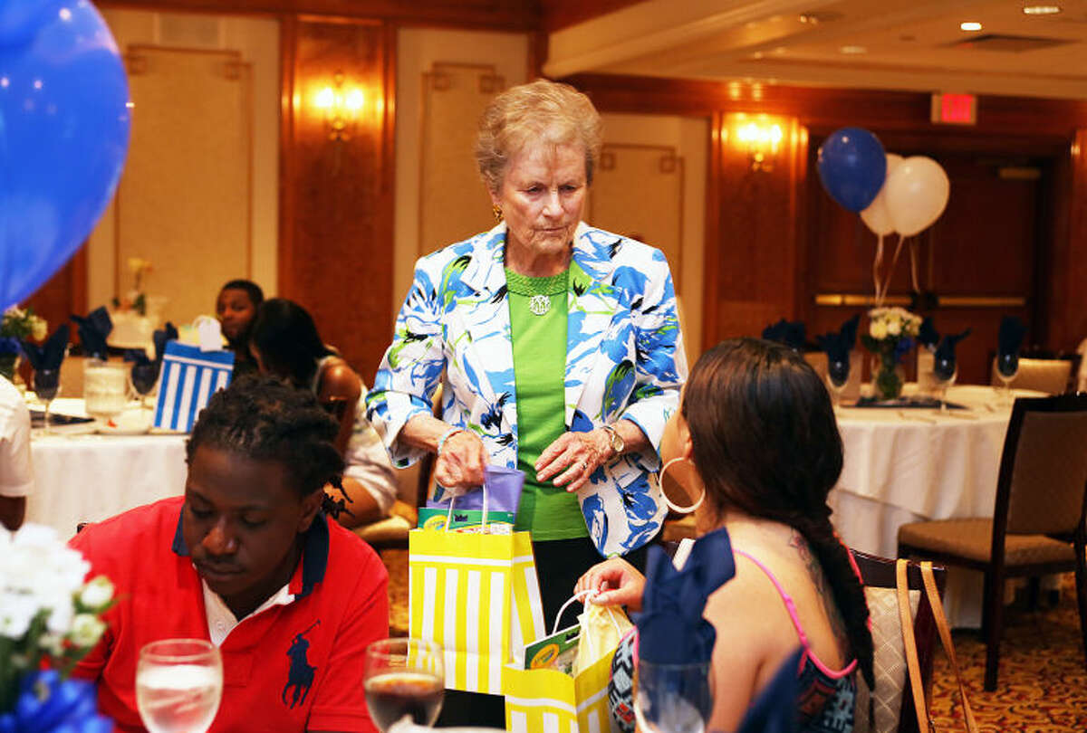 Sponsor Carol Bauer passes out gift bags during Norwalk?•s I Have a Dream Foundation's ceremony to celebrate the achievements of Washington Village students who completed the program and graduated high school and college at the Norwalk Inn Saturday evening. Hour Photo / Danielle Calloway