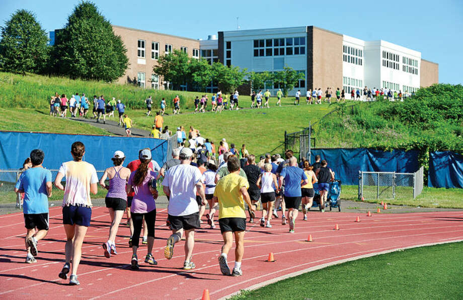 Hour photo / Erik Trautmann Runners head out in the first of 10 Westport Road Runners races Saturday, a 2.3 mile race at Staples High School.