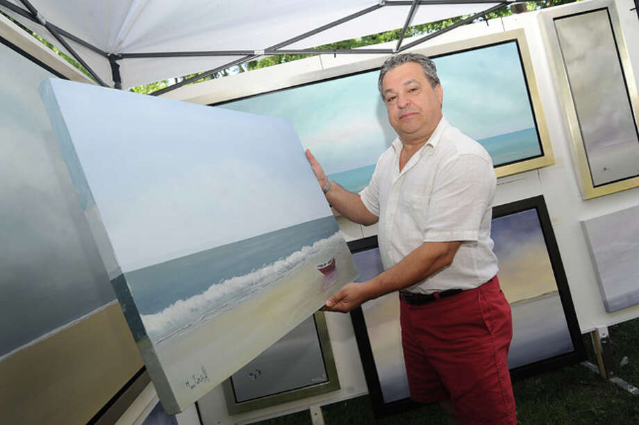Marc Fattahi with selected works on display Sunday at the Norwalk Art Festival held at Mathews Park. Hour photo/Matthew Vinci