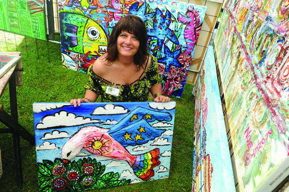 Artist Ronet Noe with some of work Sunday at the Norwalk Art Festival held at Mathews Park. Hour photo/Matthew Vinci