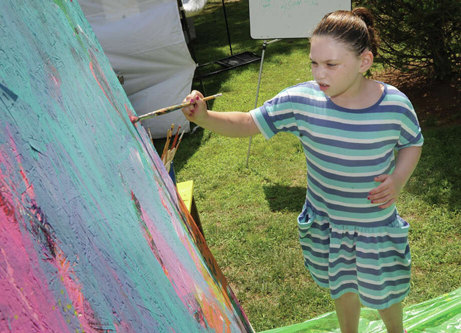 8 year old Charlie Dasl contributes brush strokes to a painting on display by Firing Circuits Studios Sunday at the Norwalk Art Festival held at Mathews Park. Hour photo/Matthew Vinci