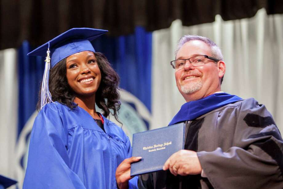 Lindsey Augustin smiles and accepts her diploma from Christian Heritage School's Head of School, Brian Modarelli at the Thirty-Third Commencement Exercises which took place in Trumbull, Conn. on Saturday, June 11, 2016. Photo: Johnathon Henninger, For Hearst Connecticut Media / Connecticut Post Freelance