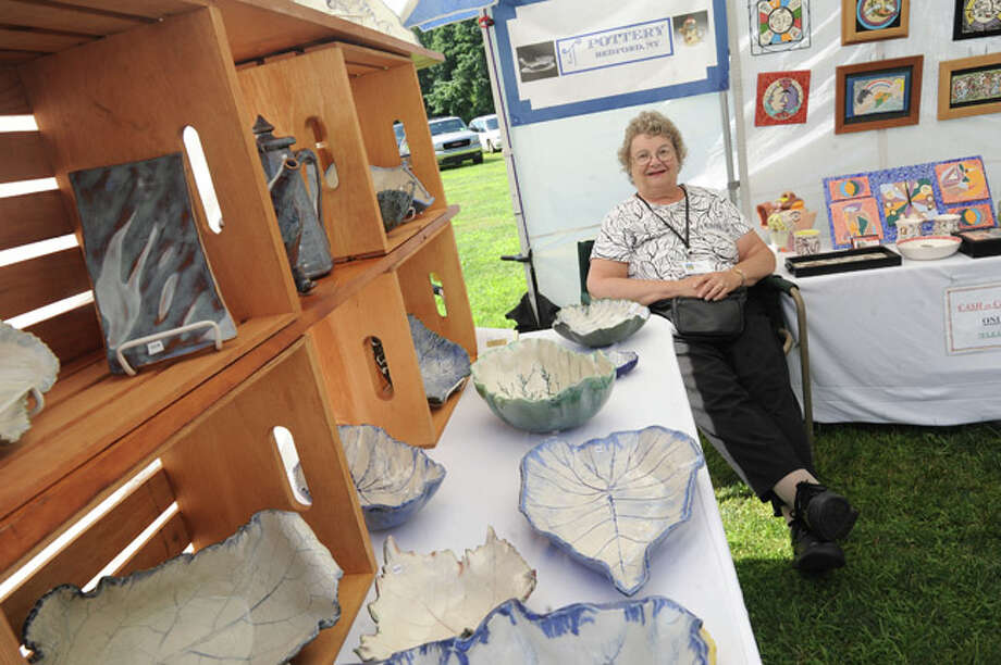 Artist Judy Tischler with some of her pottery Sunday at the Norwalk Art Festival held at Mathews Park. Hour photo/Matthew Vinci