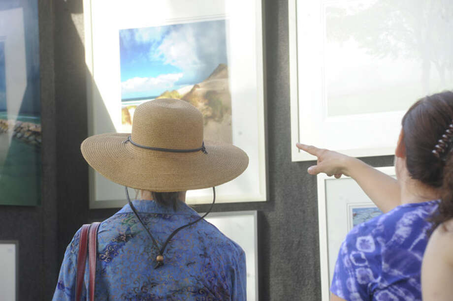 Residents admire all styles or art work Sunday at the Norwalk Art Festival held at Mathews Park. Hour photo/Matthew Vinci