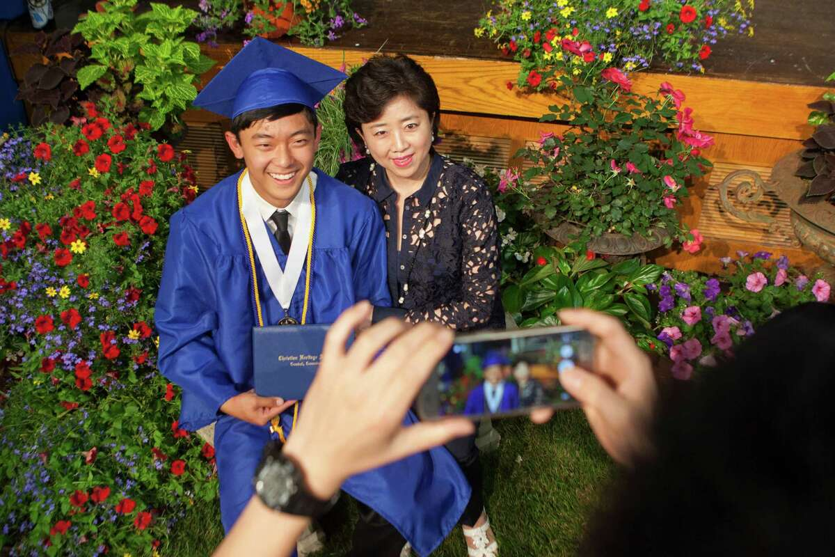 Anna Yoon sits with son, David Yoon, for a photograph after the Thirty-Third Commencement Exercises of Christian Heritage School in Trumbull, Conn. on Saturday, June 11, 2016.