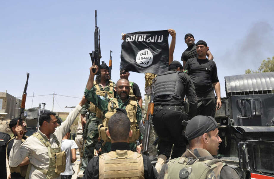 In this Saturday, June 28, 2014 photo, Iraqi security forces hold up a flag of the Islamic State in Iraq and the Levant they captured during an operation to regain control of Dallah Abbas north of Baqouba, the capital of Iraq's Diyala province, 35 miles (60 kilometers) northeast of Baghdad, Iraq. The Islamic State, which already controls vast swaths in northern and eastern Syria amid the chaos of that nation's civil war, aims to erase the borders of the modern Middle East and impose its strict brand of Shariah law. (AP Photo)