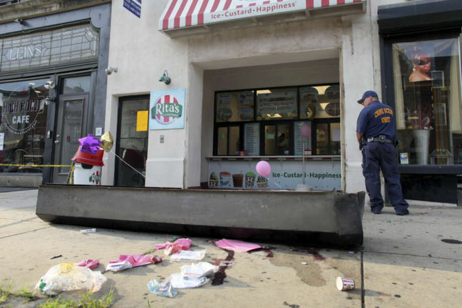 An investigator looks over the debris of a fallen security door outside a Rita's Water Ice store in the Brewerytown section of Philadelphia on Saturday, June 28, 2014. Investigators tell Philly.com that the metal security door detached and fell on a 3-year-old girl who died. (AP Photo/Joseph Kaczmarek)