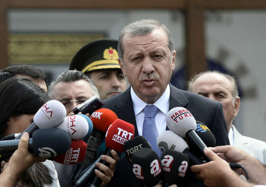 """Turkish President Recep Tayyip Erdogan speaks to the media in front of a mosque in Istanbul, Turkey, Friday, July 24, 2015. In a major tactical shift, Turkish warplanes struck Islamic State group targets Friday across the border in Syria, Turkish officials announced _ a move that came a day after IS militants fired at a Turkish military outpost, killing a soldier. In a related, long-awaited development, Erdogan confirmed that Turkey had agreed to let the U.S. use a key base in southern Turkey for military operations against the militants """"within a certain framework.""""(AP Photo/Depo Photos)"""