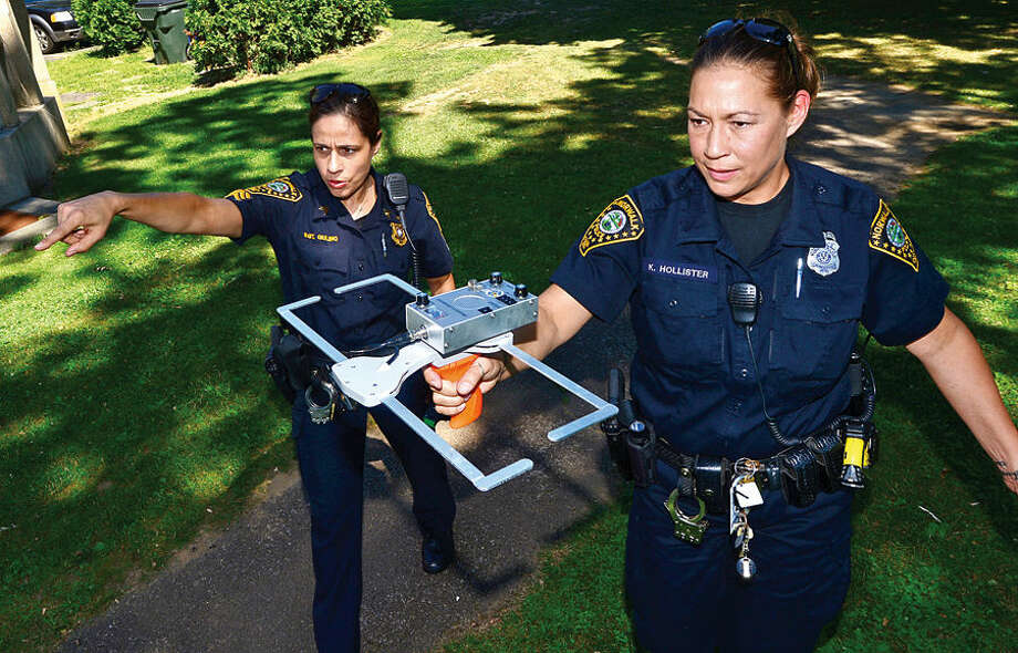 Hour photo / Erik Trautmann Norwalk police Sgt. Sofia Gulinoand officer Kelly Hollister demonstrate how their new tracking device, Project Lifesaver, works at Mathews Park Thursday. As part of the demonstration Hour reporter Robin Sattler hid herself at the park after being fitted with the transmitter and the officers were able to locate her within 10 minutes.