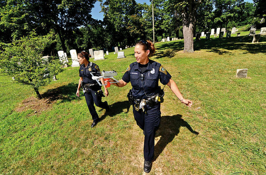 Hour photo / Erik Trautmann Norwalk police Sgt. Sofia Gulinoand officer Kelly Hollister demonstrate how their tracking device, Project Lifesaver, works at Mathews Park Thursday. As part of the demonstration Hour reporter Robin Sattler hid herself at the park after being fitted with the transmitter and the officers were able to locate her within 10 minutes.