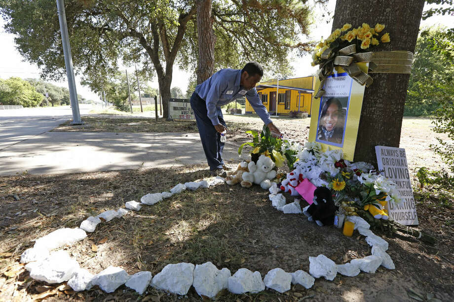 "Frank Scott visits a memorial to Sandra Bland on Thursday, July 23, 2015, in Prairie View, Texas, water a plant he had left. ""She was me,"" Scott said. ""We both moved from the crime of the big city to live in peace"" in a small town, he said. The autopsy of Bland, a black woman who was found dead in a Texas jail, revealed no injuries that would suggest she was killed by someone else, authorities said Thursday. (Steve Gonzales/Houston Chronicle via AP)"