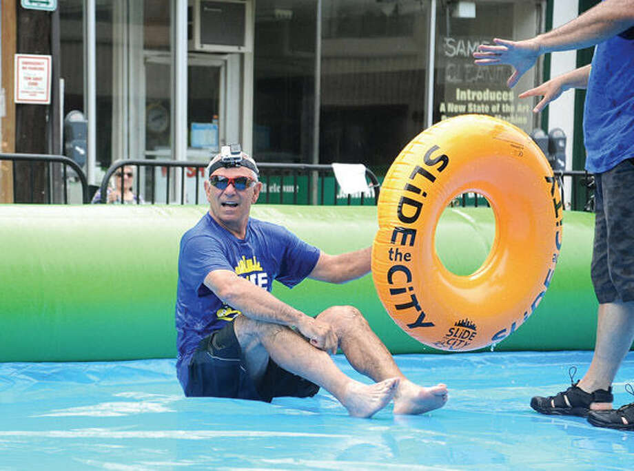 Bobby Valentine gets the first try down the giant water slide at the Slide City event held in downtown Stamford. Hour photo/Matthew Vinci