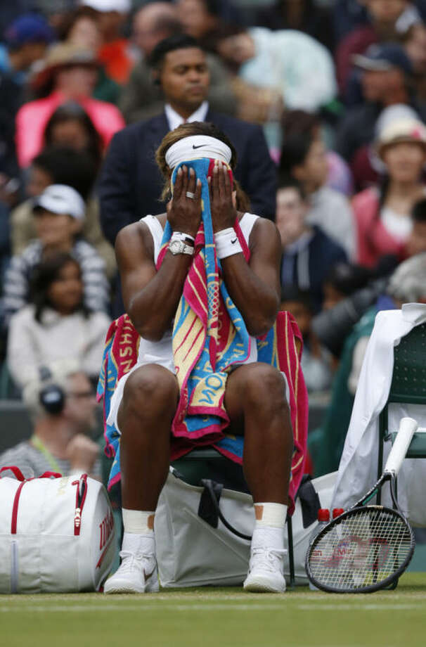 Serena Williams of U.S. covers her face with a towel between games during the women's singles match against Alize Cornet of France at the All England Lawn Tennis Championships in Wimbledon, London, Saturday, June 28, 2014. (AP Photo/Sang Tan)