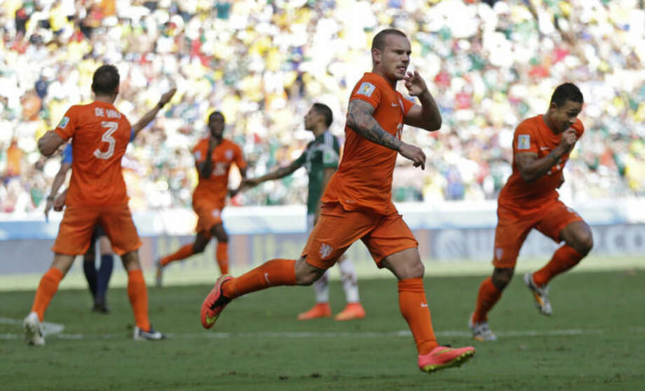Netherlands' Wesley Sneijder, center, celebrates after scoring his side's first goal during the World Cup round of 16 soccer match between the Netherlands and Mexico at the Arena Castelao in Fortaleza, Brazil, Sunday, June 29, 2014. (AP Photo/Natacha Pisarenko)