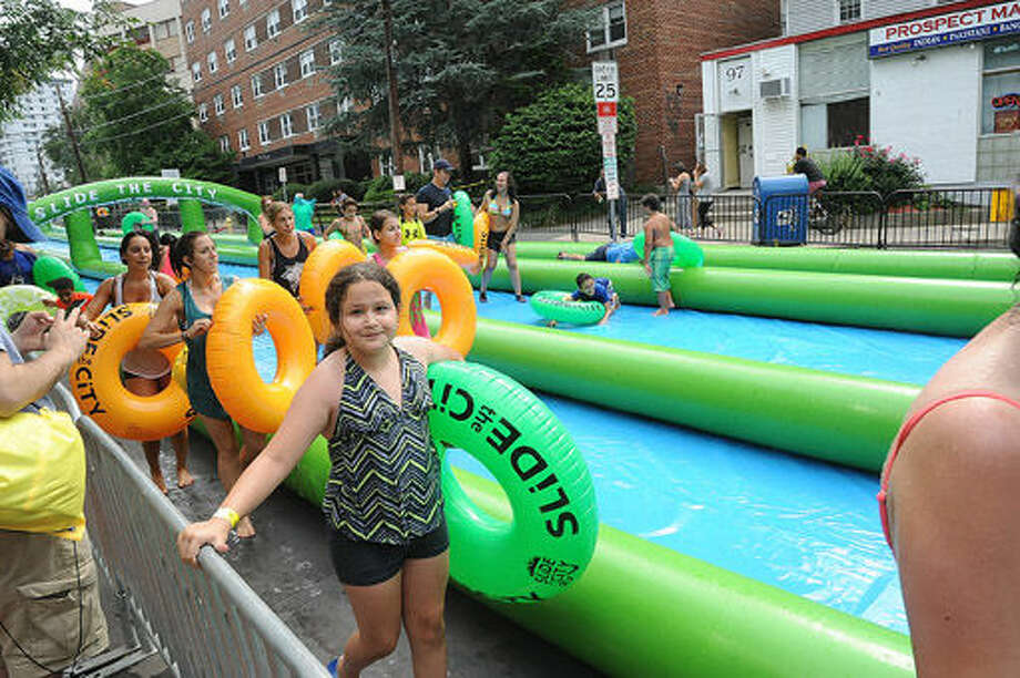 Stamford residents enjoy the giant water slide at the Slide City event held in downtown Stamford. Hour photo/Matthew Vinci