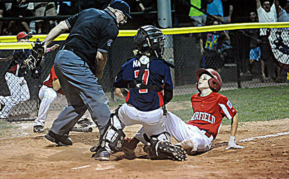 Stamford catcher Ben Nash tags out #21 Nick Morris to end the game Sunday at the Championship game between North Stamford little league and Fairfield American. Hour photo/Matthew Vinci