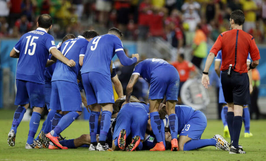 Greece's Sokratis Papastathopoulos, bottom, reacts with teammates after scoring a goal during the World Cup round of 16 soccer match between Costa Rica and Greece at the Arena Pernambuco in Recife, Brazil, Sunday, June 29, 2014. (AP Photo/Andrew Medichini)