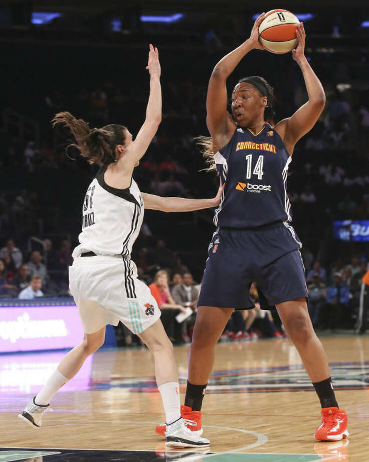 Connecticut Sun's Kelsey Bone (14) looks to pass against New York Liberty guard Anna Cruz (51) during the first half of a WNBA basketball game at Madison Square Garden in New York, Sunday, June 29, 2014. (AP Photo/John Minchillo)