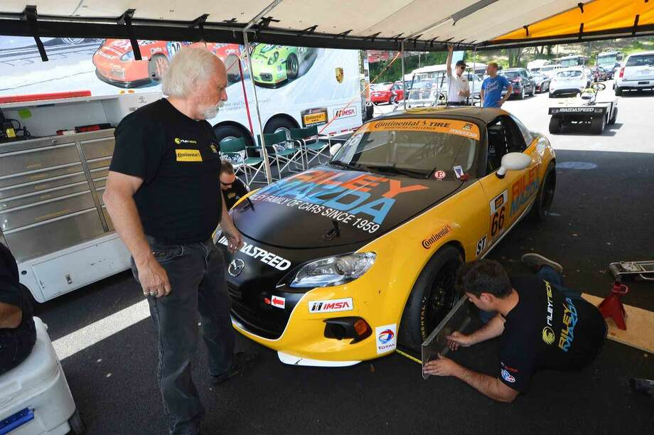 Hour Photo/Alex von Kleydorff.Stamford's Riley Mazda Team owner Chris Riley and his crew prep the car before the Continental Tire Sportscar Challenge at Lime Rock park on Saturday. with his sons AJ and Jamison as drivers they were able to qualify the Mazda Mx5 in the 38th position in ST class after running as high as 5th in the first practice session. Fuel systems issues sidelined the car just 5 laps in and they finished in 39th place